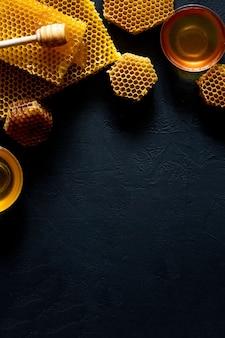 Miel avec nid d'abeille sur table noire, vue de dessus. espace pour le texte.