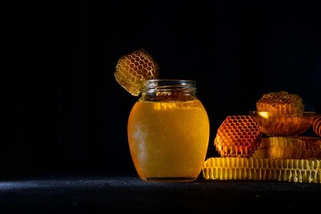 Miel avec nid d'abeille sur table noire