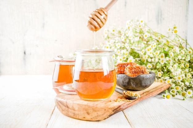 Miel en petit pot avec pollen et rayons de miel