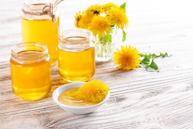Miel de pissenlit dans un pot et fleurs fraîches sur table en bois blanc