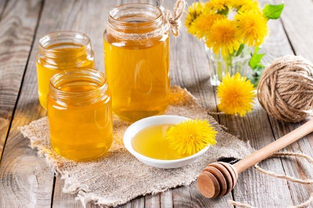 Miel de pissenlit dans un pot et fleurs fraîches sur une table en bois