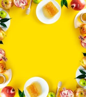Miel, pomme et grenade sur fond jaune. concept nouvel an juif joyeuses fêtes roch hachana. disposition créative des symboles traditionnels. vue d'en-haut. espace de copie. cadre pour cartes.