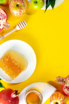 Miel, pomme et grenade sur fond jaune. concept nouvel an juif joyeuses fêtes roch hachana. disposition créative des symboles traditionnels. vue d'en-haut. mise à plat. espace de copie. shana tova.