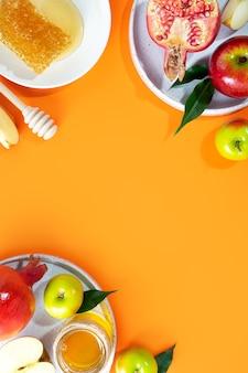 Miel pomme et grenade sur fond orange concept nouvel an juif joyeuses fêtes rosh
