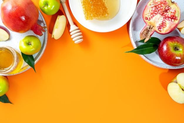 Miel pomme et grenade sur fond orange concept nouvel an juif roch hachana