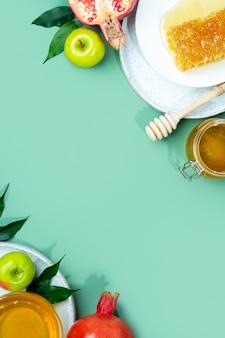 Miel pomme et grenade sur un fond vert menthe concept nouvel an juif roch hachana