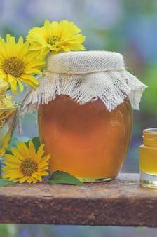 Miel en pot avec une louche à miel sur une table en bois rustique. miel doux dans le peigne. concept d'aliments sains. produits de miel par des ingrédients biologiques.