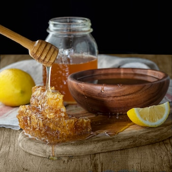 Miel en pot avec nid d'abeille et bruine en bois au citron sur une table en bois. fond sombre