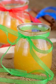 Miel en pots sur une table en bois à côté des bâtons de cannelle et d'une cuillère