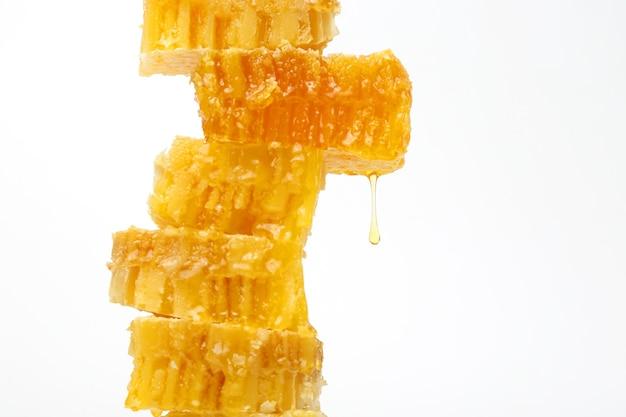 Miel qui coule des nids d'abeilles sur fond clair