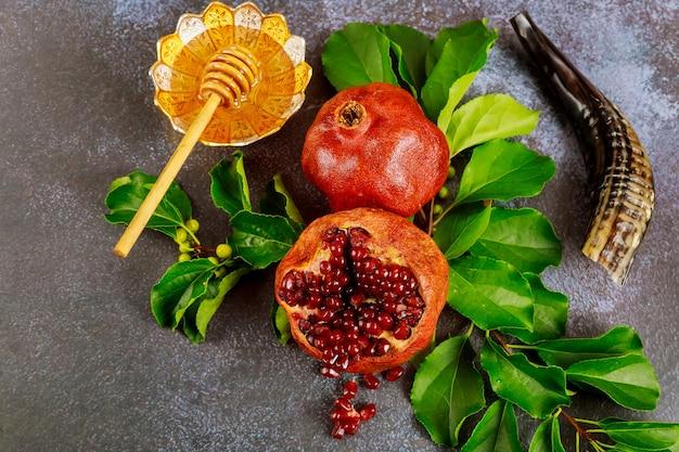 Miel sucré traditionnel avec bâton en bois et fruits pour la fête juive de rosh hashanah.