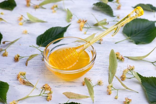 Miel de tilleul en pot et bol avec une louche de miel sur une table en bois blanc