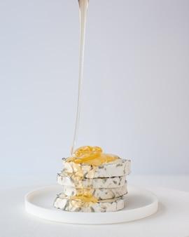 Le miel tombe sur des tranches de fromage de chèvre moulées