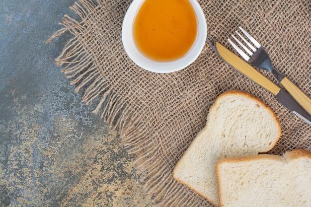 Miel, tranches de pain et couverts sur toile de jute.