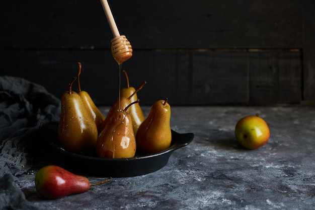 Miel versé poires cuites sur une assiette