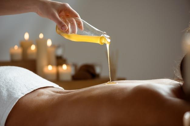 Miel verser sur le dos nu de la femme dans le salon spa.