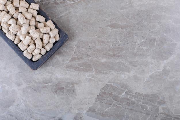 Miettes de biscuits dans le plateau, sur la surface en marbre