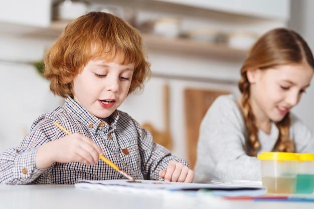 Mieux ensemble. enfant aux cheveux roux engagé enthousiaste utilisant un pinceau et des aquarelles peignant ses idées sur le papier tout en passant du temps avec sa sœur