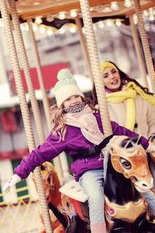 Mieux ensemble. incroyable fille blonde gardant le sourire sur son visage tout en montant un carrousel