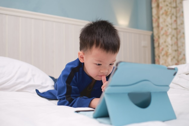 Mignon asiatique 3-4 ans enfant garçon enfant souriant tout en jouant au jeu, en regardant un dessin animé, en utilisant un ordinateur tablette pc, des enfants accros aux gadgets, une tablette d'apprentissage pour les enfants, un concept de jouet éducatif pour tout-petits