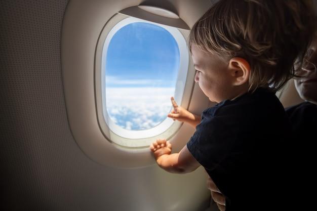 Mignon bambin pointe son doigt vers le ciel à travers la fenêtre. concept de premier vol, voyageant avec des enfants.