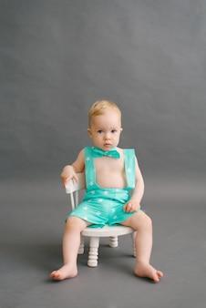 Mignon beau garçon avec un noeud papillon est assis sur une petite chaise blanche