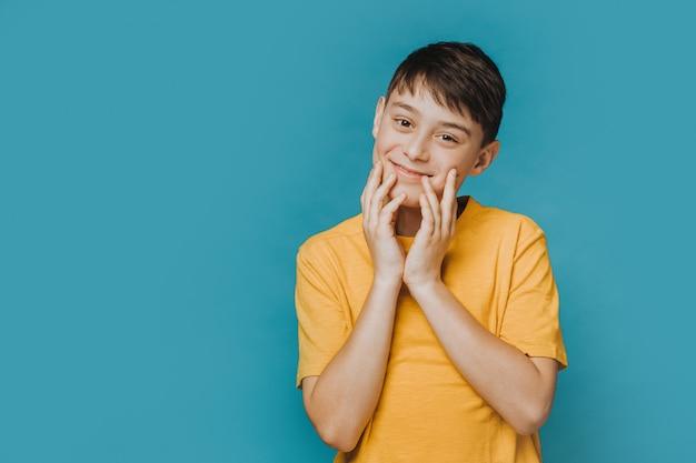 Mignon beau garçon en t-shirt jaune touchant son visage, regardant avec tendresse, se sent caresse, heureux d'être en bonne santé et d'avoir de bons amis