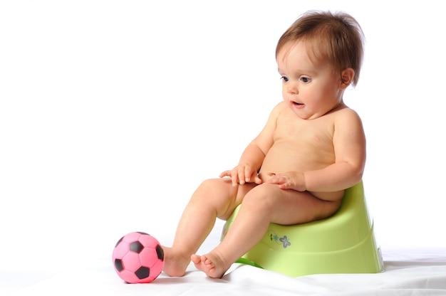 Mignon bébé drôle d'un an assis sur un pot vert.
