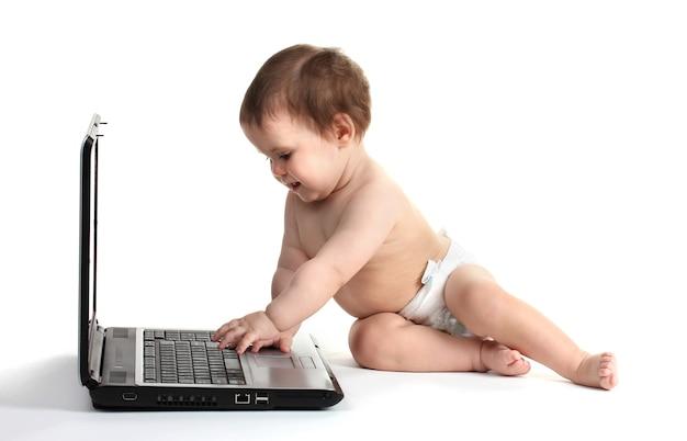 Mignon bébé fille et ordinateur portable isolé sur blanc