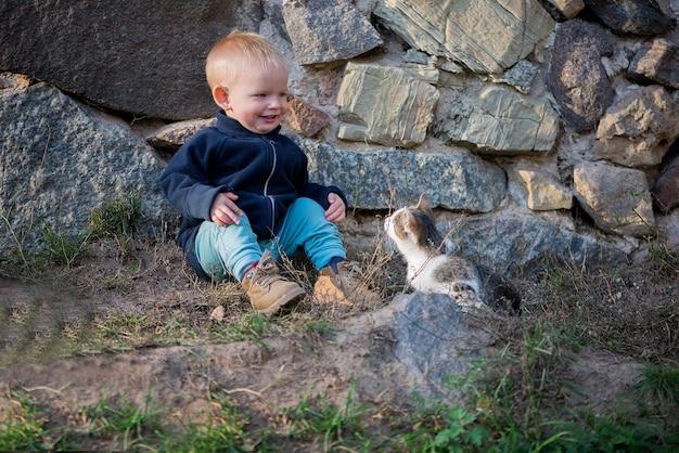 Mignon bébé garçon et chat assis à l'extérieur