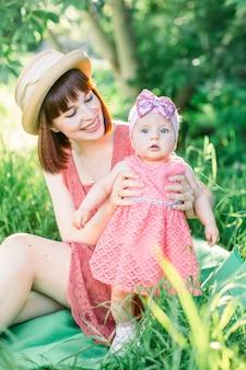 Mignon bébé heureux drôle faisant ses premiers pas sur une herbe verte, la mère tenant ses mains soutenant en apprenant à marcher