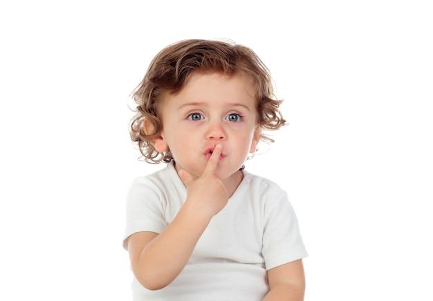 Mignon bébé a mis l'index sur les lèvres comme signe de silence