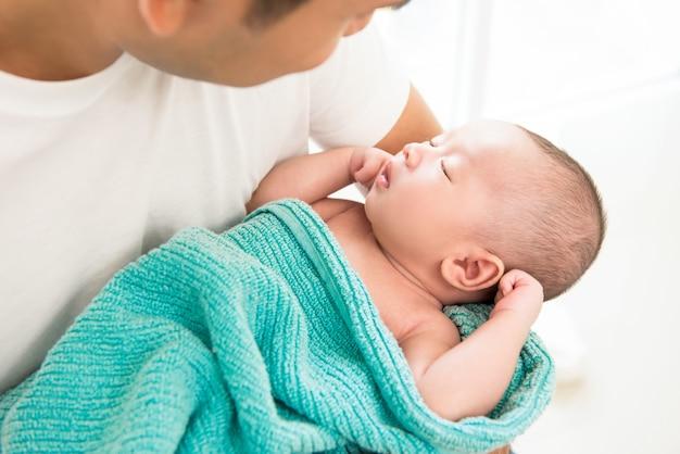 Mignon bébé nouveau-né dort dans les bras de son père