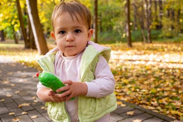 Mignon bébé sérieux tout-petit tenant un téléphone jouet dans le parc.