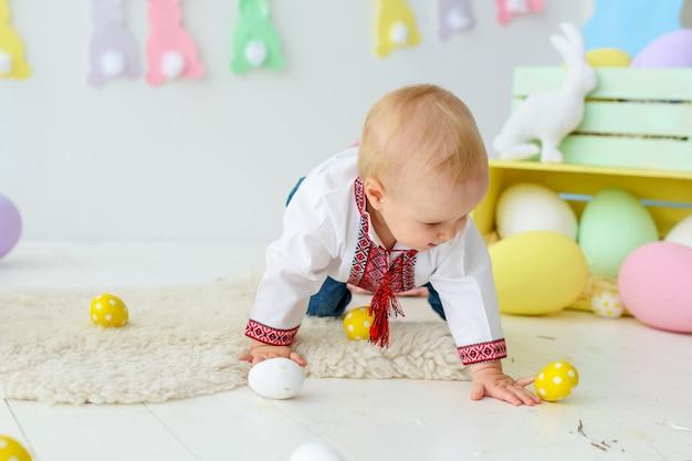 Mignon bébé souriant en broderie traditionnelle dans des décorations de pâques colorées