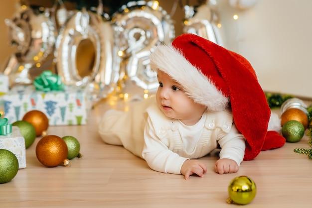 Mignon bébé souriant est couché sous un arbre de noël festif et joue avec des cadeaux. célébrations de noël et du nouvel an.