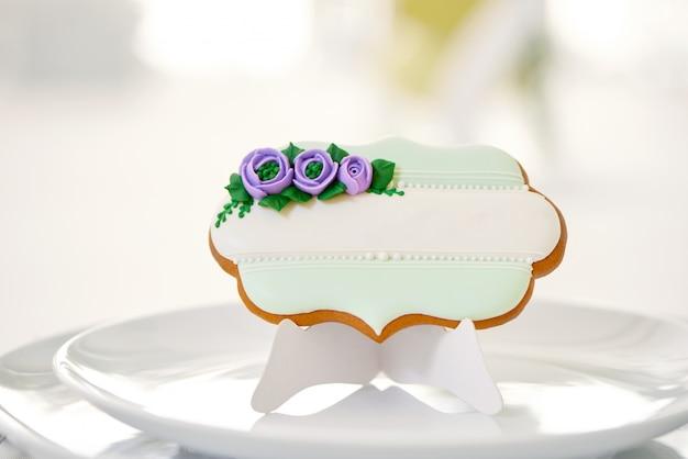 Mignon biscuit de pain d'épice sucré avec des fleurs et des perles de glaçage bleu et vert se dresse sur une plaque blanche sur une table de restaurant, recouverte d'une nappe blanche comme neige. décoration parfaite pour table de fête.