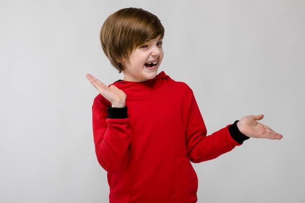 Mignon confiant caucasien petit garçon souriant heureux en pull rouge sur fond gris