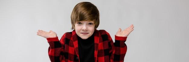 Mignon confiant perplexe petit garçon caucasien en chemise à carreaux sur un mur gris