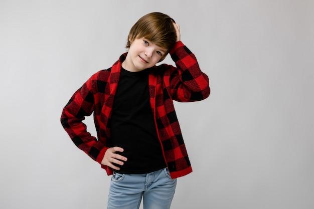 Mignon doux souriant petit garçon caucasien en chemise à carreaux