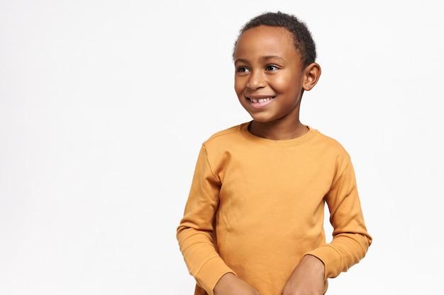 Mignon écolier afro-américain en sweat-shirt jaune posant contre un mur blanc avec copie espace pour votre information