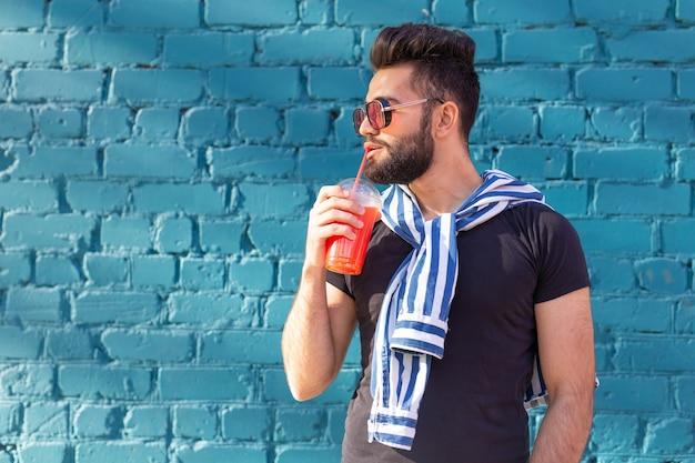 Mignon élégant jeune hipster mâle arabe avec une moustache et une barbe et portant des lunettes de boire du jus avec une paille. concept de vacances d'été.