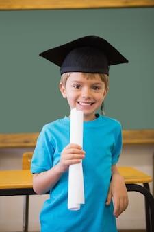 Mignon élève dans un conseil de mortier souriant à la caméra dans la salle de classe
