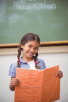 Mignon élève souriant à la caméra lors de la présentation de la classe