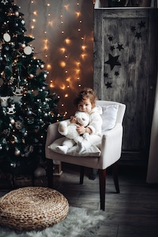 Mignon enfant bouclé avec un ours en peluche assis dans un fauteuil près d'un arbre de noël joliment décoré