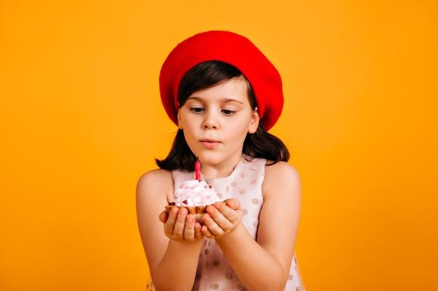 Mignon enfant brune faisant le souhait d'anniversaire. fille préadolescente en béret rouge souffle la bougie sur le gâteau.