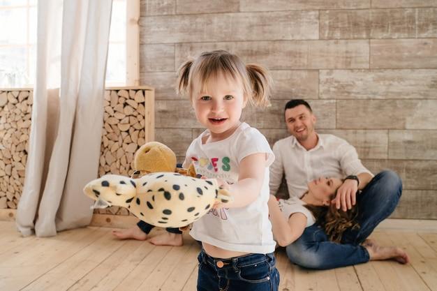 Mignon enfant fille et papa chatouillant maman s'amusant bon moment à jouer ensemble à la maison, parents heureux et petite fille enfant appréciant l'activité et la communication drôle, famille riant détente