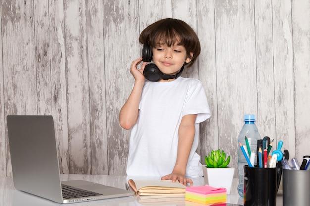 Mignon, enfant, garçon, dans, t-shirt blanc, noir, écouteurs, utilisation, gris, ordinateur portable, table, à, vert, plante