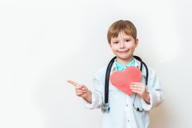 Mignon enfant garçon en uniforme de médecin avec stéthoscope et coeur à la main sur blanc