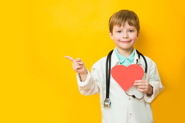 Mignon enfant garçon en uniforme de médecin avec stéthoscope et coeur en main jaune